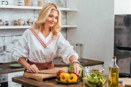 Photo pour Blonde femme adulte préparer la salade pour le dîner à la maison - image libre de droit