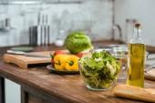 vegetables for salad and bottle of olive oil on tabletop in kitchen