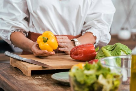 Photo for Cropped image of woman preparing salad for dinner and holding bell pepper at home - Royalty Free Image