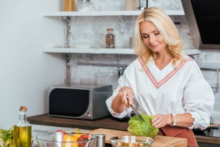 Photo for Adult blonde woman preparing salad for dinner and cutting cabbage at home - Royalty Free Image