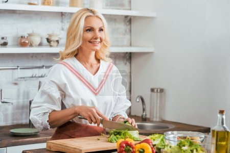 Photo for Smiling attractive adult woman preparing salad for dinner, cutting cabbage and looking away at home - Royalty Free Image