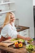 """Постер, картина, фотообои """"привлекательная женщина готовит салат на ужин и положить ингредиенты в миске на дому"""""""