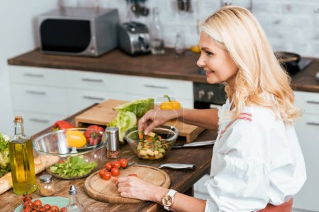 Photo for Side view of smiling adult woman preparing salad for dinner at home - Royalty Free Image