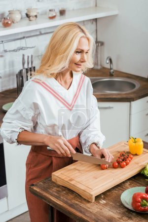 attractive adult woman preparing salad for dinner and cutting cherry tomatoes at home