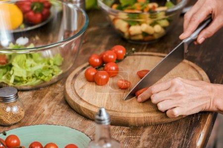 Photo pour Cropped image de la femme préparant la salade pour le dîner et la coupe de tomates cerises à la maison - image libre de droit