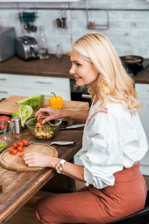Photo for Side view of attractive adult woman preparing salad for dinner at home - Royalty Free Image