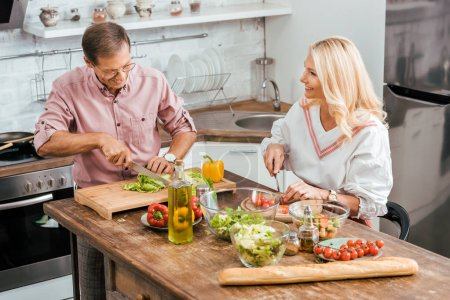 Photo for Smiling adult husband and wife preparing salad for dinner together and cutting vegetables in kitchen - Royalty Free Image