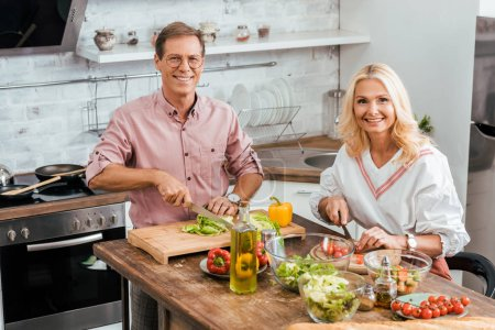Photo for High angle view of smiling couple preparing salad for dinner together in kitchen and looking at camera - Royalty Free Image
