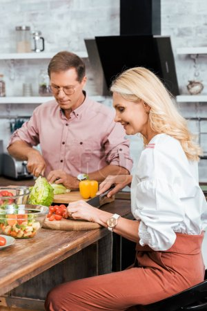 Photo for Smiling couple preparing salad for dinner together and cutting vegetables in kitchen - Royalty Free Image