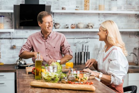Photo for Smiling couple preparing salad for dinner together in kitchen, looking at each other - Royalty Free Image