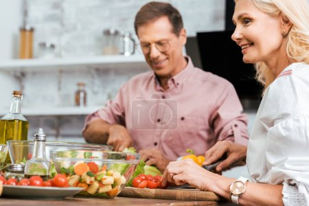 Photo for Smiling wife and husband preparing salad for dinner together in kitchen - Royalty Free Image