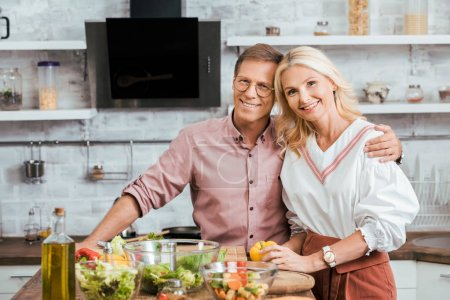 Photo for Affectionate adult couple hugging and looking at camera during salad preparation for dinner in kitchen - Royalty Free Image