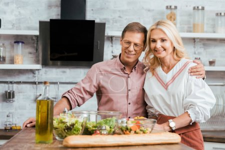 adult smiling couple preparing salad for dinner at home