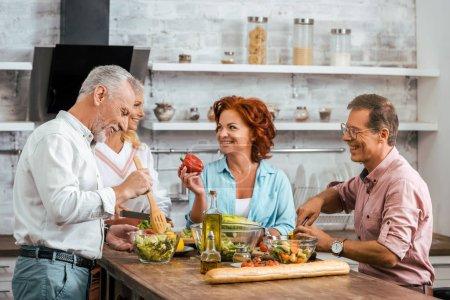 Photo pour Sourire des amis adultes préparant la salade pour le dîner et de parler à la maison - image libre de droit