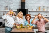 mature men having fun with vegetables during preparing salad for dinner at home and looking at camera