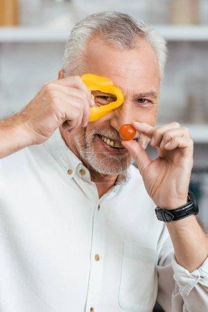 Photo pour Bel homme souriant, s'amuser avec des légumes au cours de la préparation de salade pour le dîner à la maison - image libre de droit