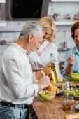 mature friends preparing organic salad for dinner at home