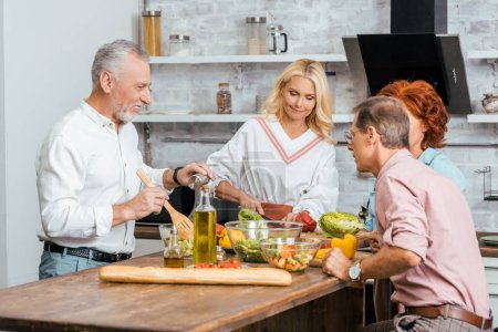 Photo for Mature men and women preparing salad for dinner at home - Royalty Free Image