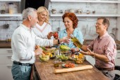 mature male and female friends preparing salad for dinner at home
