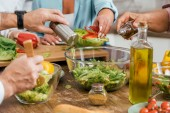 cropped image of mature friends preparing salad for dinner at home and adding spices in bowl