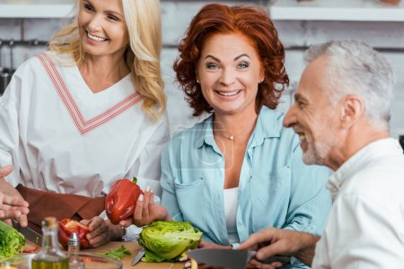 Photo pour Rire les amis matures préparant la salade pour le dîner à la maison - image libre de droit