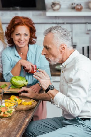 Photo for Mature couple having salad for dinner at home - Royalty Free Image