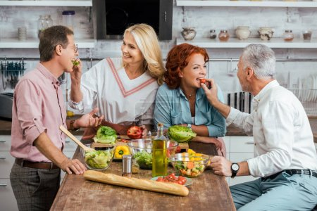 Photo for Happy mature couples feeding each other during salad preparation for dinner at home - Royalty Free Image