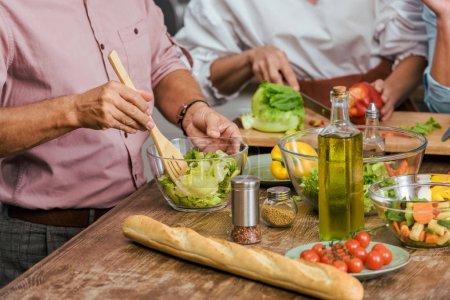 Photo pour Image recadrée d'amis matures préparant la salade pour le dîner ensemble à la maison - image libre de droit