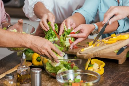 cropped image of mature friends preparing salad for dinner at home
