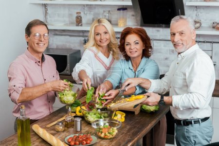 smiling mature friends preparing salad for dinner at home and looking at camera