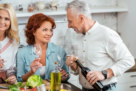 smiling mature couple looking at each other during friend meeting at home