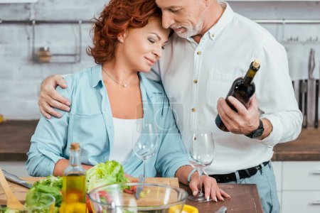 affectionate husband hugging wife during salad preparation for dinner in kitchen and holding wine bottle