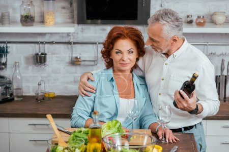 Photo for Handsome husband hugging attractive wife during salad preparation for dinner in kitchen - Royalty Free Image