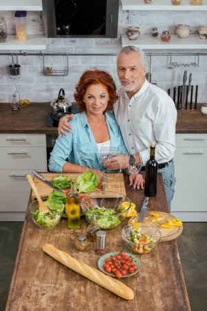 Photo for High angle view of husband hugging wife during salad preparation for dinner in kitchen - Royalty Free Image