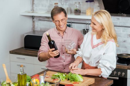 beautiful wife preparing salad for dinner at home, smiling husband holding wine bottle and wineglasses