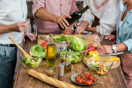 cropped image of man pouring wine to happy old friends during dinner in kitchen, vegetables on tabletop