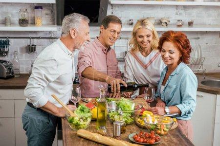 Photo pour Bel homme versant du vin à de vieux amis heureux pendant le dîner à la maison - image libre de droit