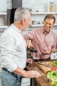 handsome happy man pouring wine to old friend during dinner in kitchen