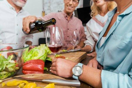 Photo pour Cropped image de vin verseur bel homme à de vieux amis heureux pendant le dîner dans la cuisine - image libre de droit