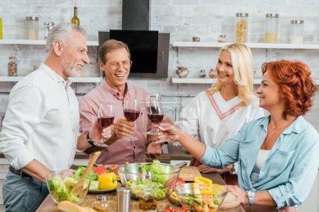Photo pour Souriants vieux amis tinter les verres à vin en cuisine - image libre de droit