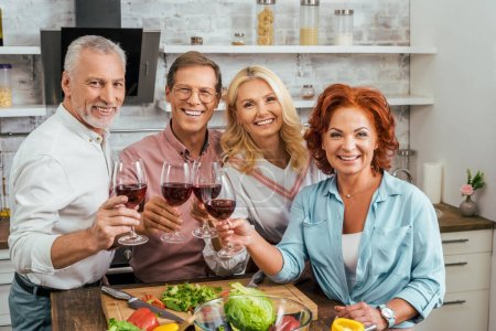 smiling old friends clinking with wineglasses in kitchen and looking at camera