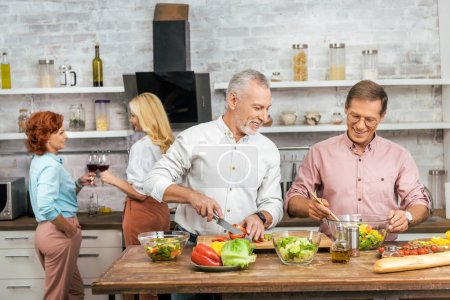 handsome smiling men preparing salad for dinner at home, women talking with wine