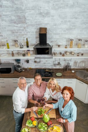 high angle view of old friends clinking with wineglasses in kitchen and looking at camera
