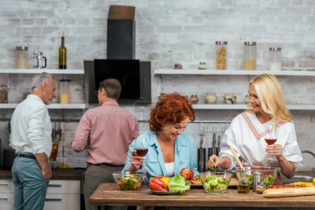 laughing beautiful women preparing salad for dinner and holding wineglasses at home