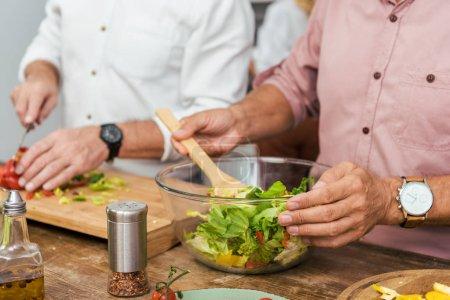 cropped image of men preparing salad for dinner at home