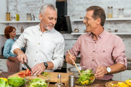 handsome smiling men preparing salad for dinner at home
