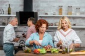smiling attractive women preparing salad for dinner, men talking with wine at home