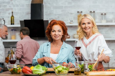 smiling beautiful women preparing salad for dinner with wine and looking at camera at home