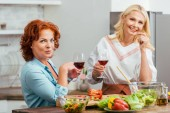 smiling attractive women preparing salad for dinner, holding wineglasses and looking at camera at home