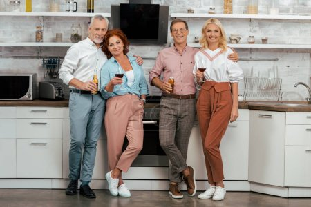 two happy mature couples holding alcoholic beverages and smiling at camera in kitchen